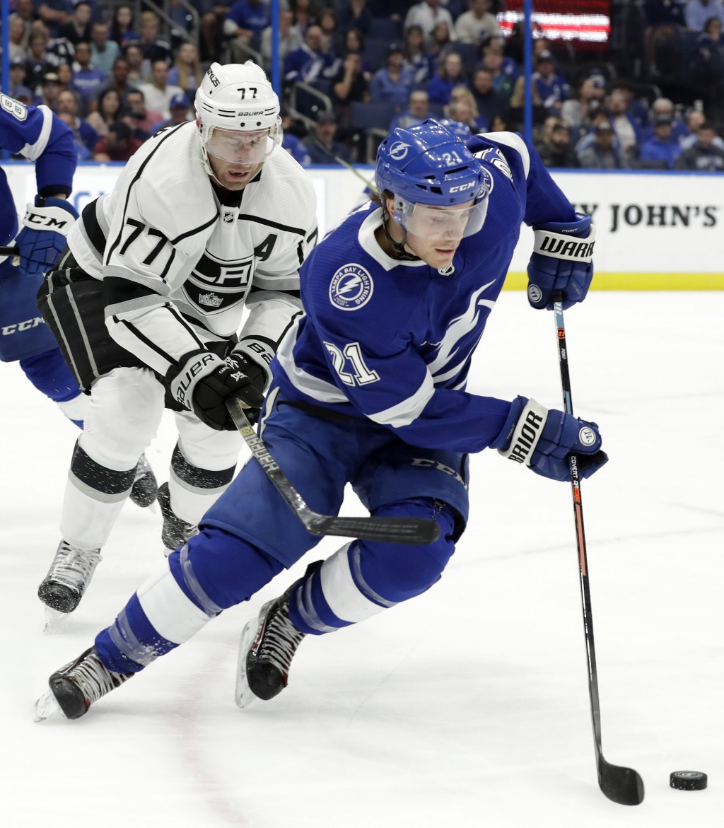 Tampa Bay Lightning center Brayden Point (21) gets around Los Angeles Kings center Jeff Carter (77) during the first period of an NHL hockey game Mond...
