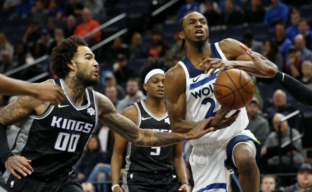 Sacramento Kings' Willie Cauley-Stein, left, knocks the ball away from Minnesota Timberwolves' Andrew Wiggins, right, in the first half of an NBA bask