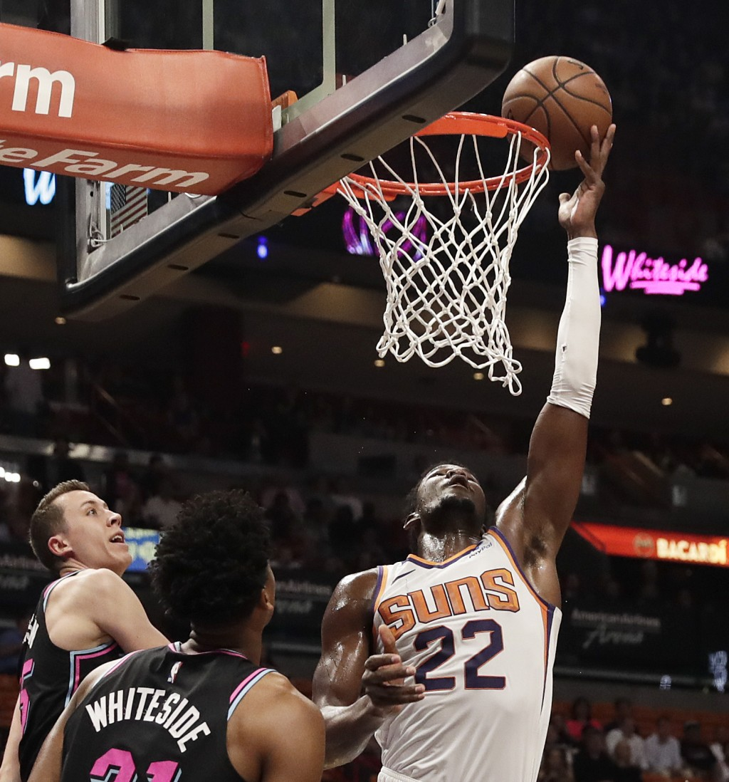 Phoenix Suns center Deandre Ayton (22) shoots and scores against Miami Heat forward Duncan Robinson (55) and Miami Heat center Hassan Whiteside (21) d...