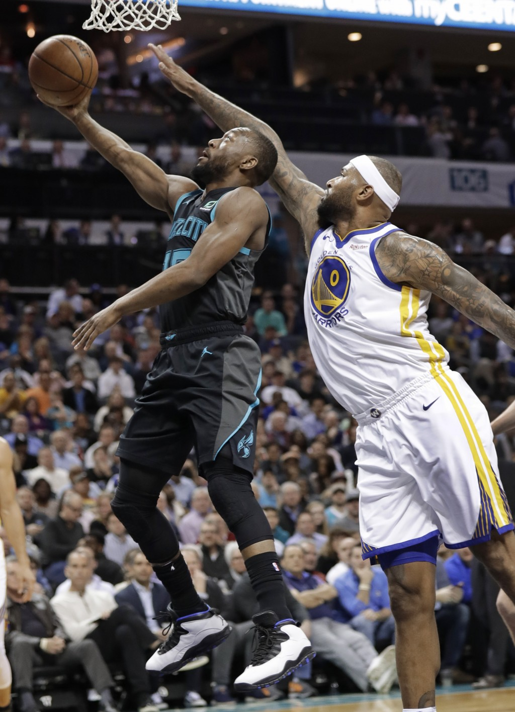 Charlotte Hornets' Kemba Walker (15) drives past Golden State Warriors' DeMarcus Cousins (0) during the first half of an NBA basketball game in Charlo