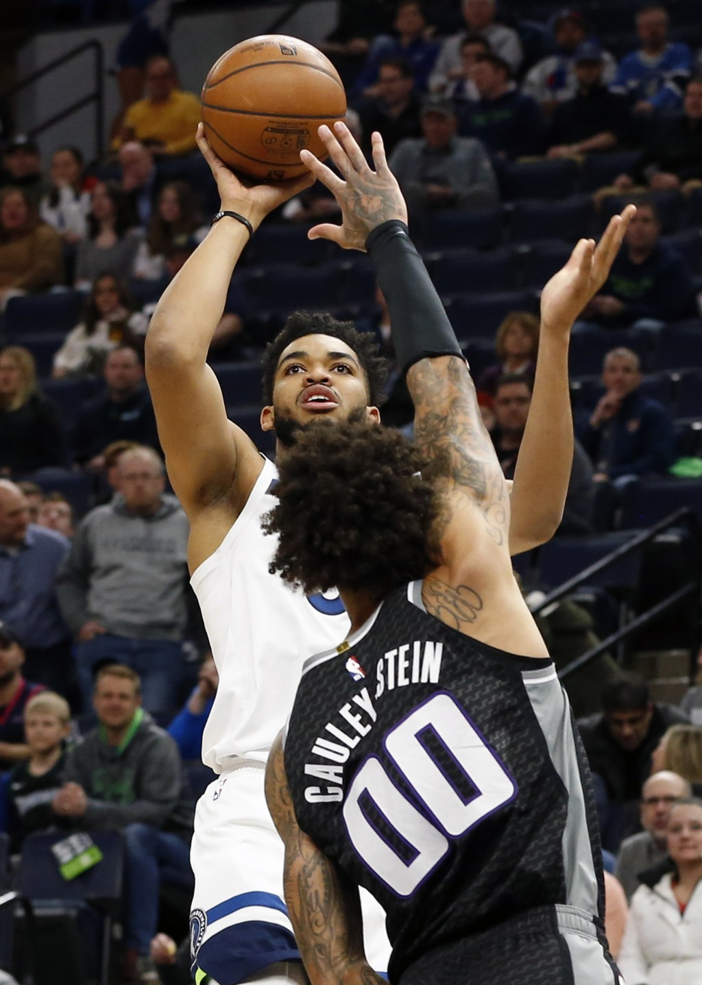 Minnesota Timberwolves' Karl-Anthony Towns, left, shoots over Sacramento Kings' Willie Cauley-Stein in the first half of an NBA basketball game Monday
