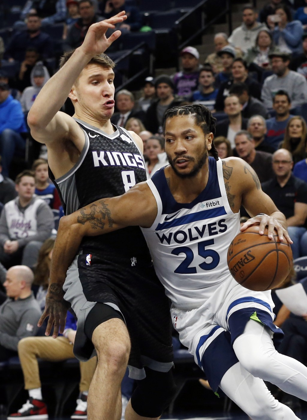 Minnesota Timberwolves' Derrick Rose, right, drives around Sacramento Kings' Bogdan Bogdanovic in the first half of an NBA basketball game Monday, Feb