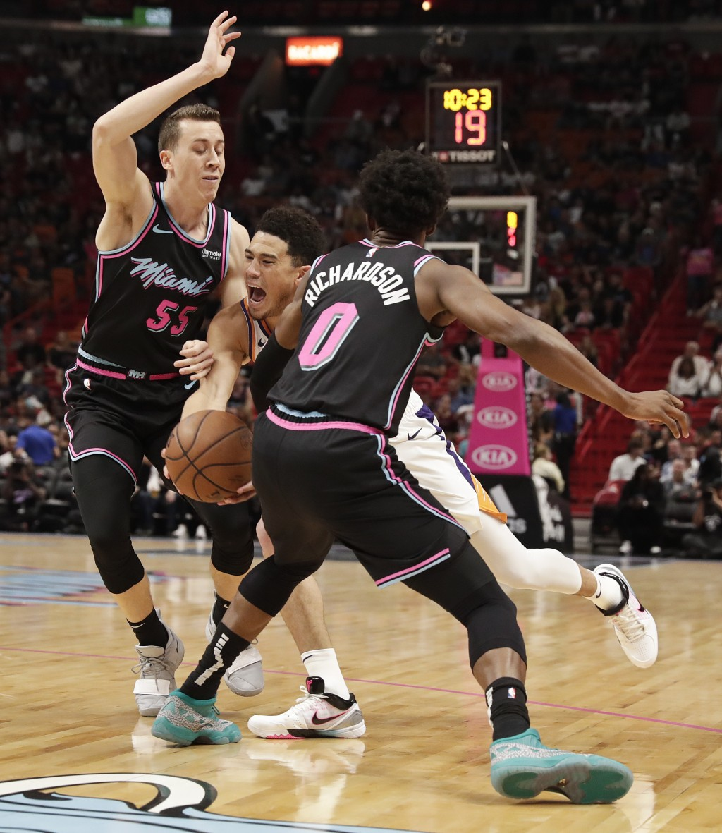 Phoenix Suns guard Devin Booker, center, pushes through Miami Heat forward Duncan Robinson (55) and guard Josh Richardson (0) during the first half of