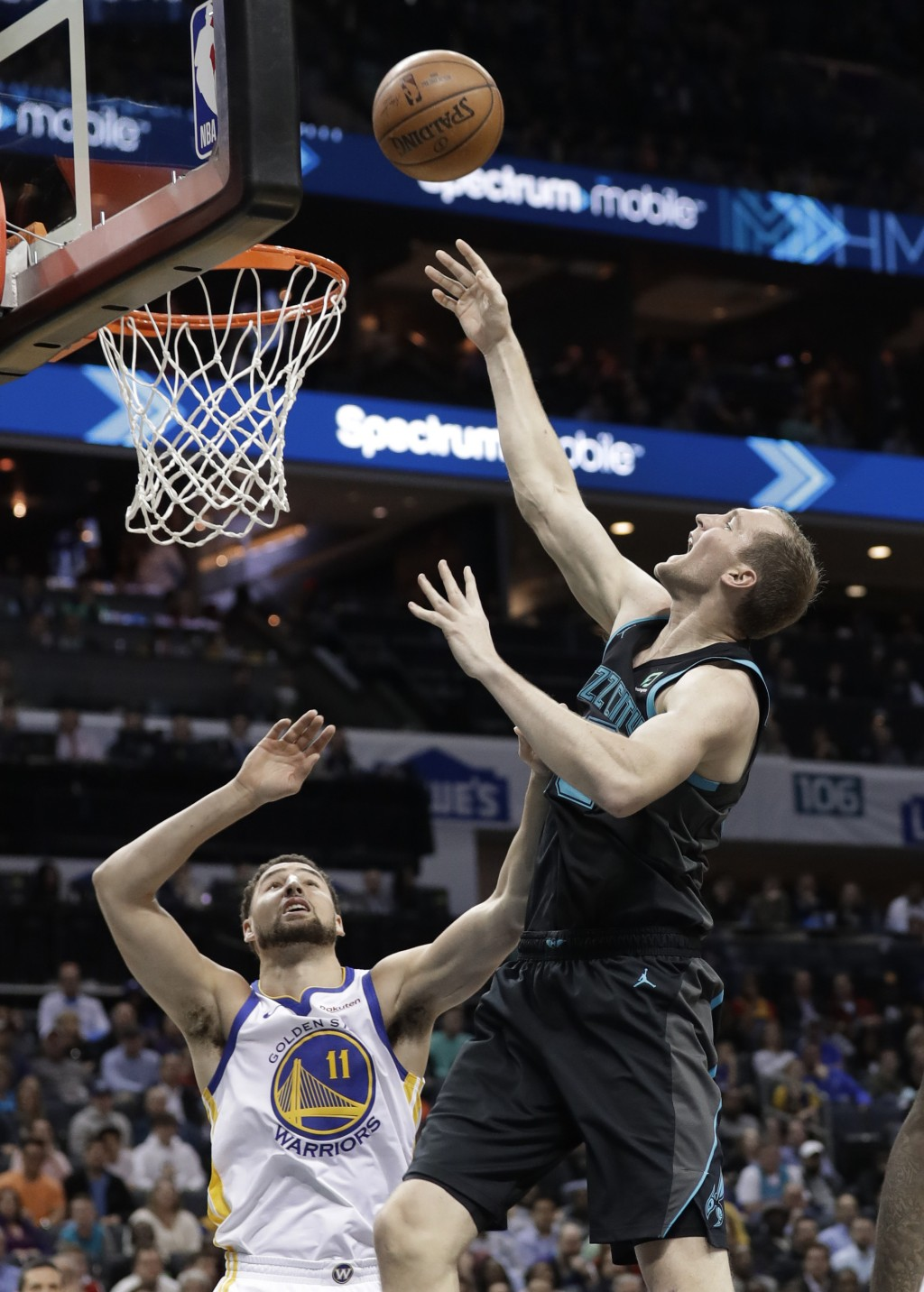 Charlotte Hornets' Cody Zeller, right, drives against Golden State Warriors' Klay Thompson (11) during the first half of an NBA basketball game in Cha