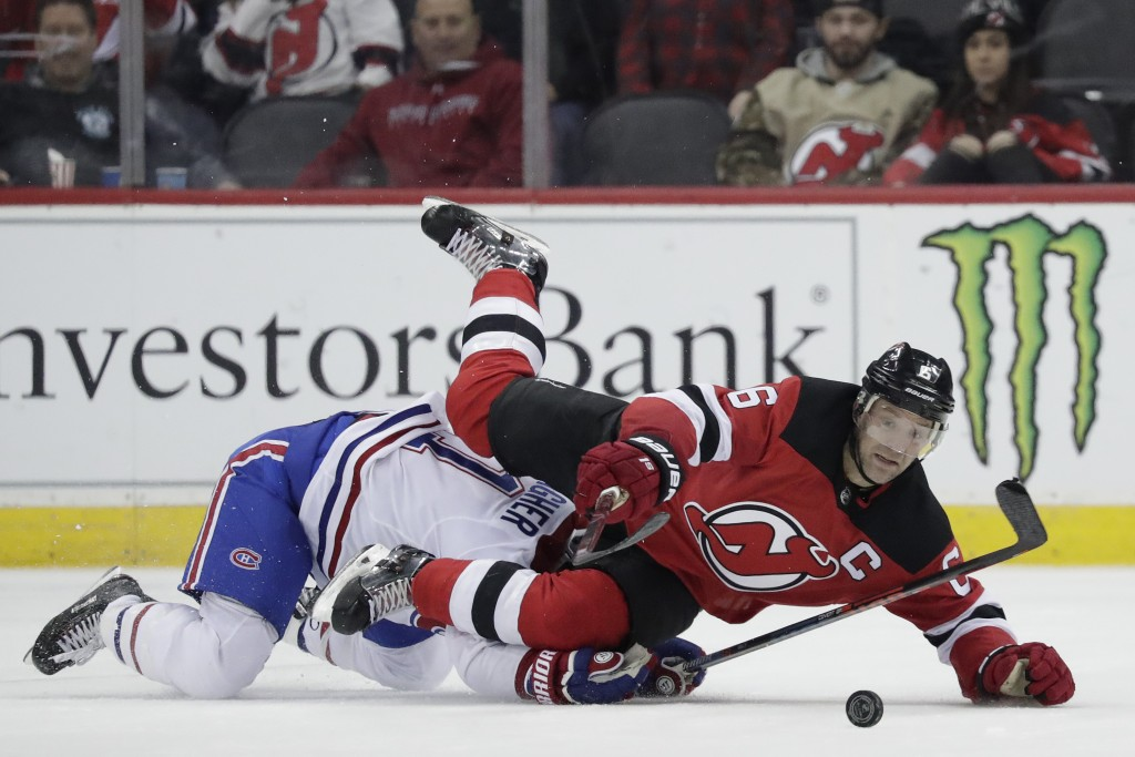 New Jersey Devils defenseman Andy Greene (6) is tripped by Montreal Canadiens right wing Brendan Gallagher (11) during the second period of an NHL hoc...