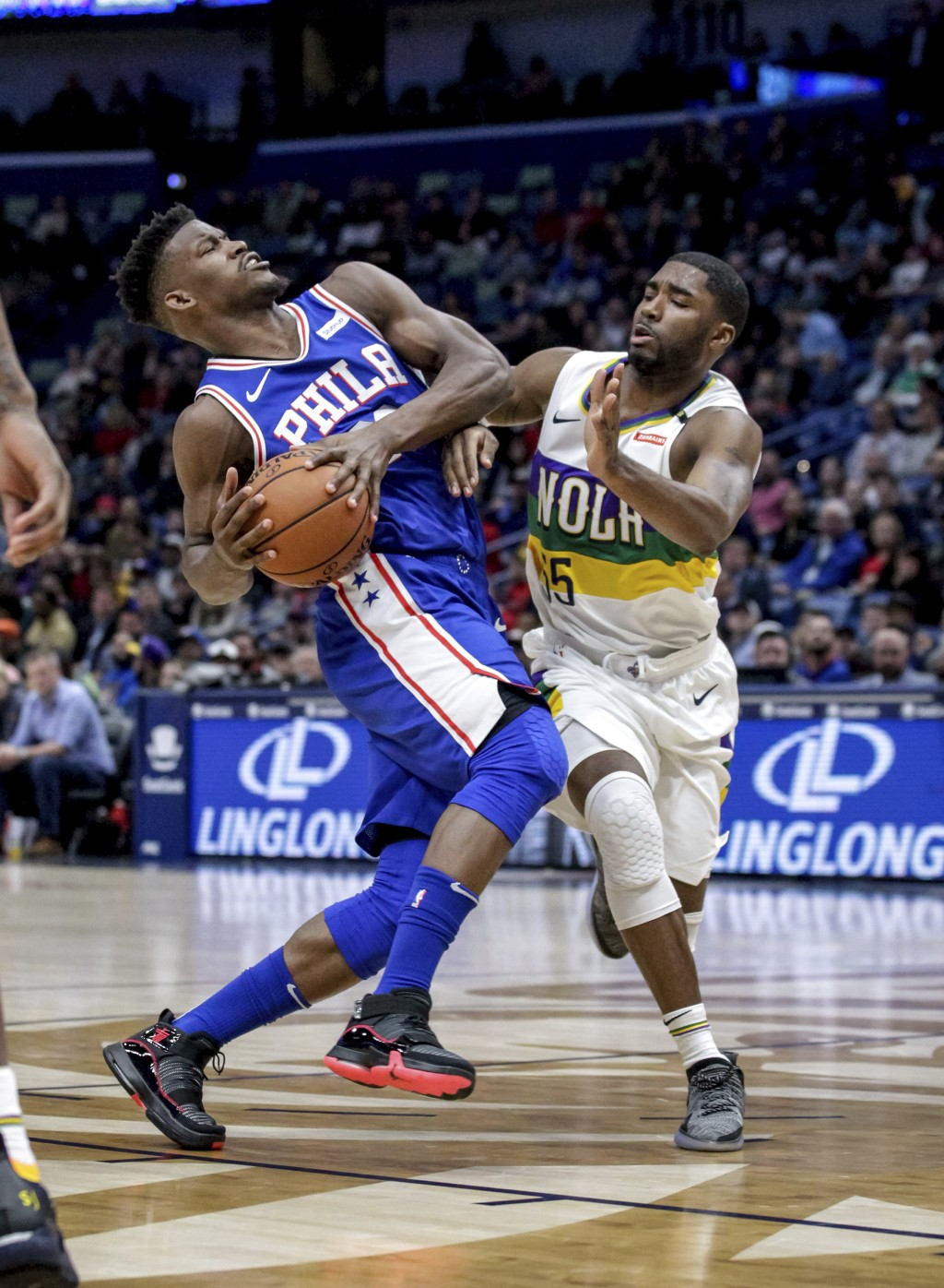 Philadelphia 76ers guard Jimmy Butler, left, drives against New Orleans Pelicans guard E'Twaun Moore (55) in the first half of an NBA basketball game ...
