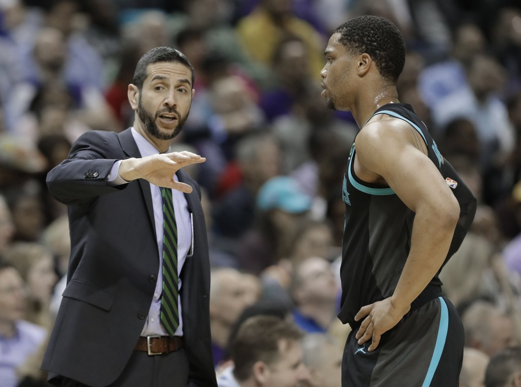 Charlotte Hornets head coach James Borrego, left, talks with Miles Bridges, right, during the first half of an NBA basketball game against the Golden