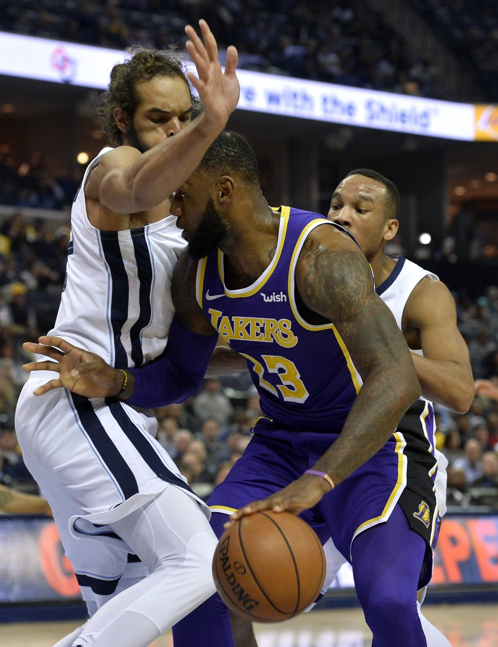Los Angeles Lakers forward LeBron James (23) handles the ball between Memphis Grizzlies center Joakim Noah, left, and guard Avery Bradley in the first