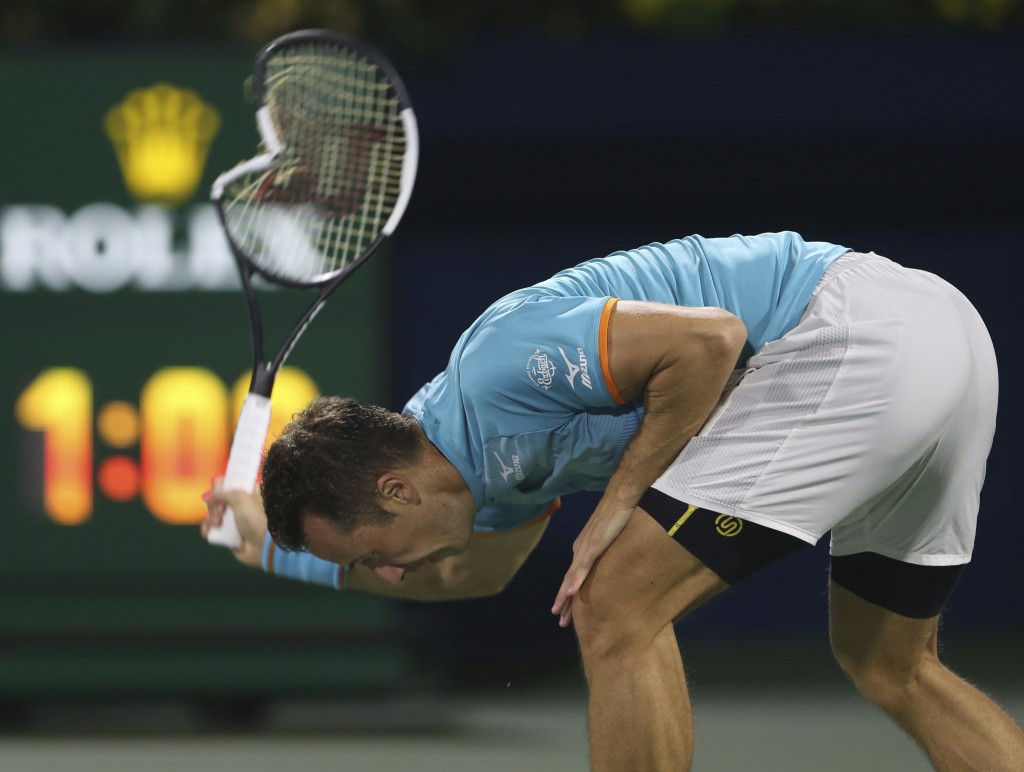 Philipp Kohlschreiber of Germany breaks his racket in a match against Roger Federer of Switzerland during the Dubai Duty Free Tennis Championship, in