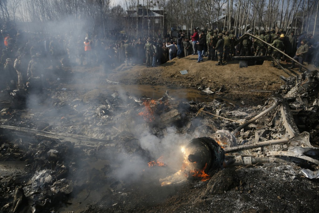 Kashmiri villagers and Indian army soldiers gather near  the wreckage of an Indian aircraft after it crashed in Budgam area, outskirts of Srinagar, In