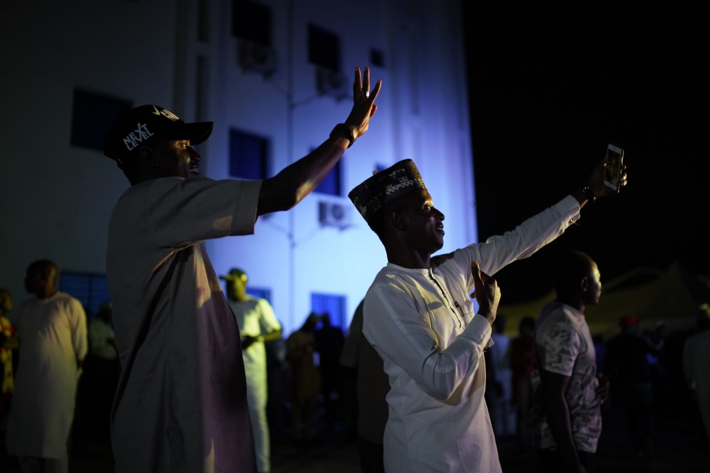 Supporters of Incumbent President Muhammadu Buhari take selfies at Buhari's campaign headquarters as they wait for the results to be officially announ...