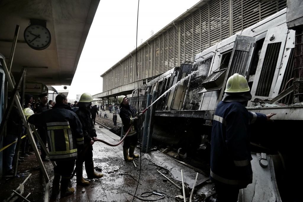 Firefighters hose down a train that was damaged after a crash inside Ramsis train station in Cairo, Egypt, Wednesday, Feb. 27, 2019. An Egyptian medic