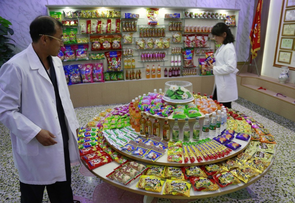 FILE - In this Oct. 22, 2018, file photo, Kwon Yong Chol, left, the chief engineer at the Songdowon General Foodstuffs Factory, shows samples of produ...