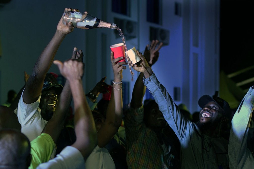 Supporters of Incumbent President Muhammadu Buhari pour champagne anticipating a win as they wait for the results to be officially announced in Abuja,...
