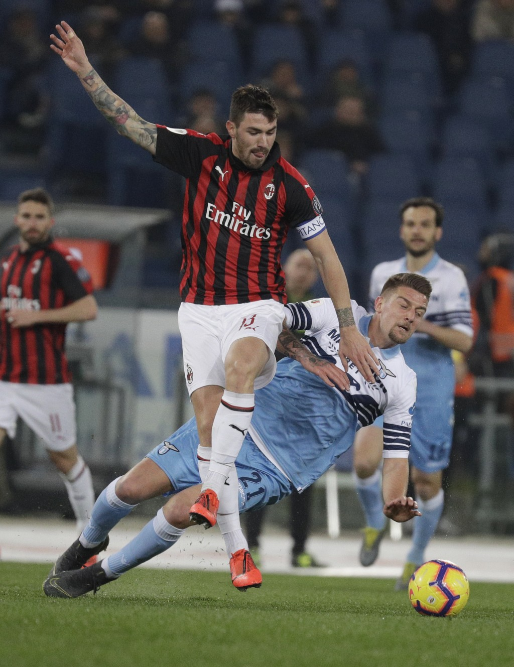 FILE - In this Tuesday, Feb.26, 2019 filer, Lazio's Sergej Milinkovic-Savic, right is tackled by AC Milan's Alessio Romagnoli during the Italian Cup,