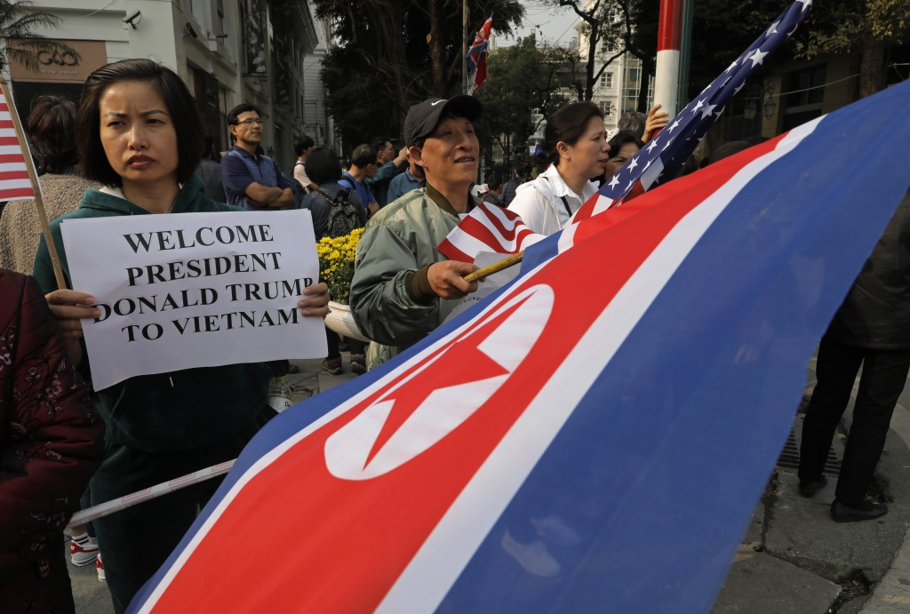 People hold placards and U.S. and North Korea flags outside the Metropole hotel where U.S. President Donald Trump and North Korean leader Kim Jong Un