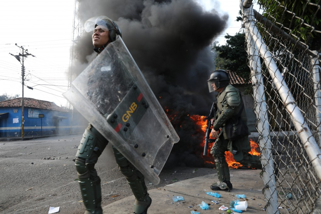 FILE - In this Feb. 23, 2019 file photo, officers of the Bolivarian National Guard run during clashing with residents who cleared a barricaded border