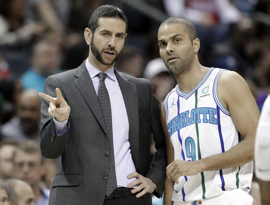 Charlotte Hornets head coach James Borrego, left, talks with Tony Parker, right, during the first half of an NBA basketball game against the Houston R
