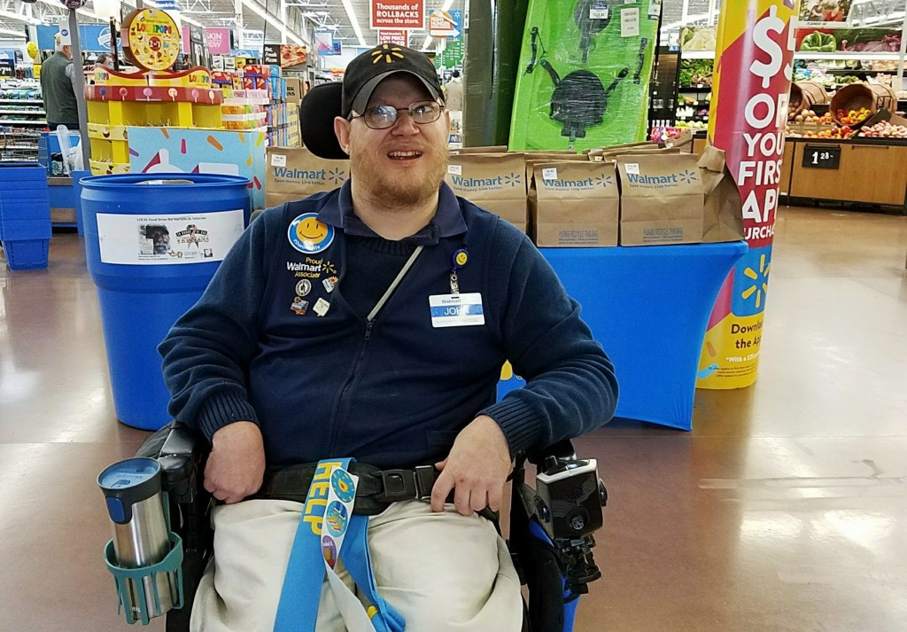 In this April 21, 2018 photo provided by Rachel Wasser, Walmart greeter John Combs works at a Walmart store in Vancouver, Wash. Combs, who has cerebra...
