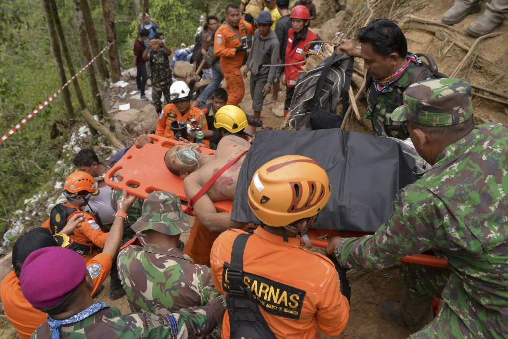 Rescuers carry a survivor of a collapsed mine on a stretcher in Bolaang Mongondow, North Sulawesi, Indonesia, Thursday, Feb. 28, 2019.  Rescuers have
