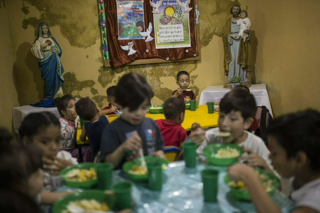 FILE - In this Feb. 11, 2019 file photo, children have lunch in the San Antonio de Padua soup kitchen in Petare slum of Caracas, Venezuela. In the thr