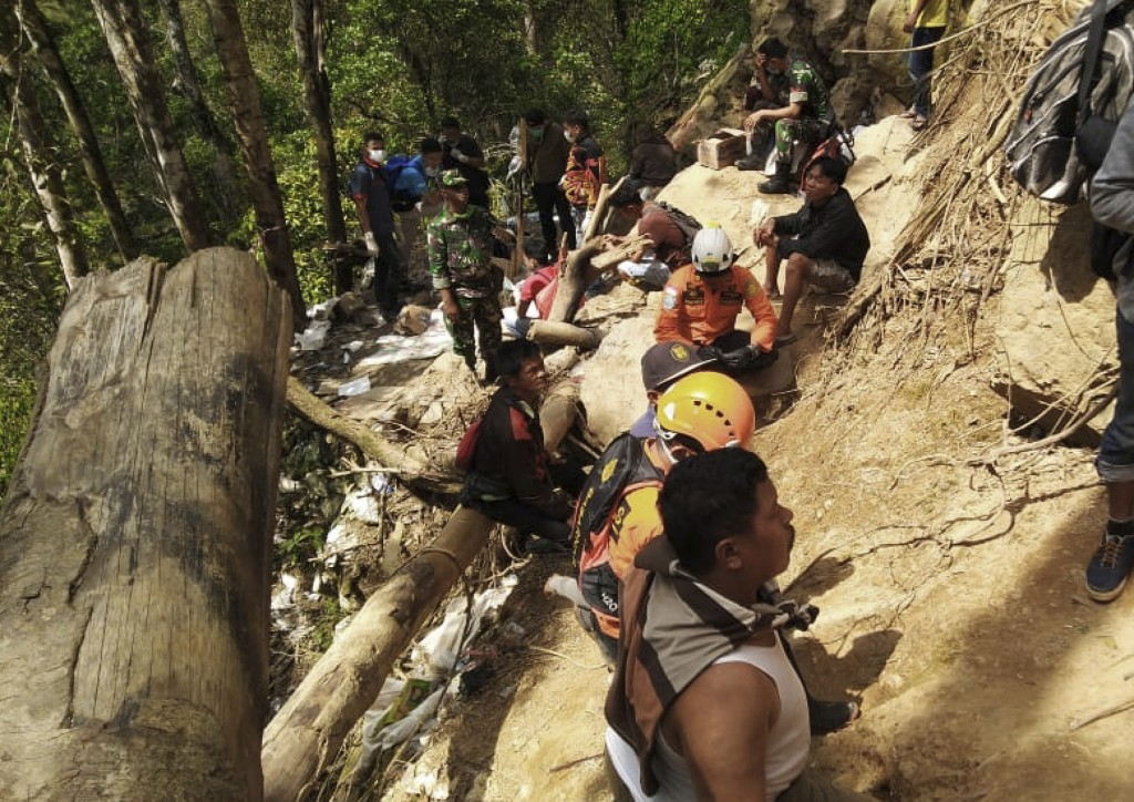 Rescuers take a break near the entrance of a collapsed mine in Bolaang Mongondow, North Sulawesi, Indonesia, Thursday, Feb. 28, 2019. Rescue workers u