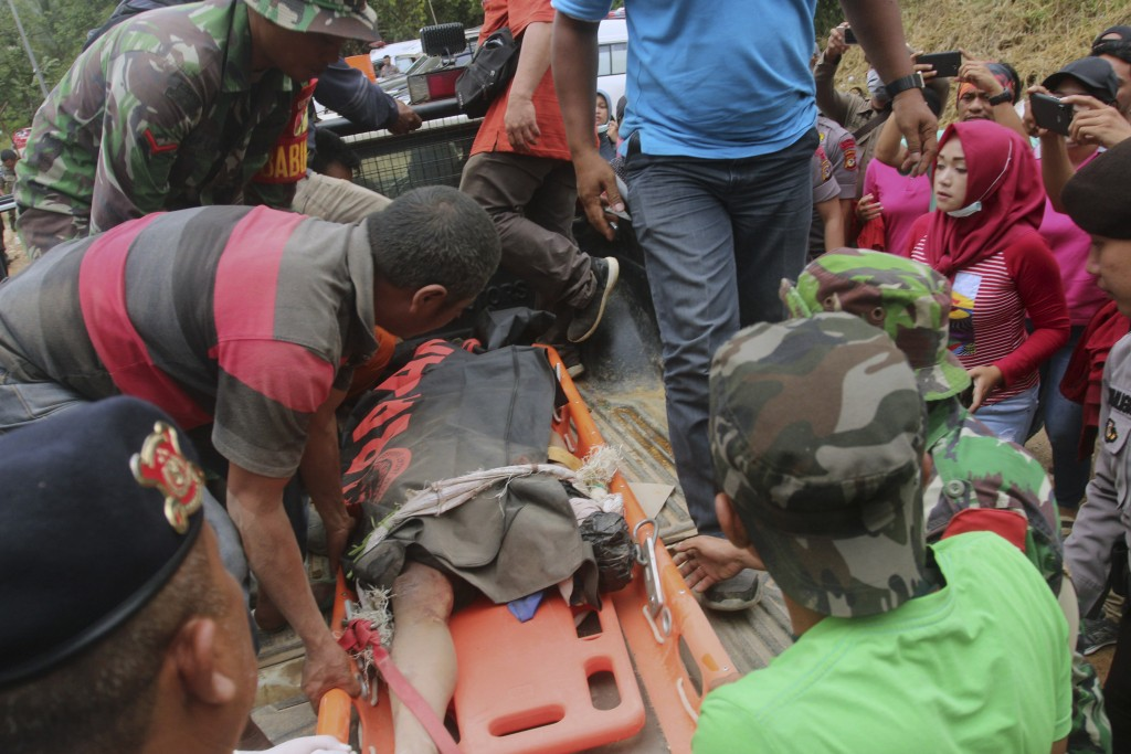Rescuers load the body of a victim of a collapsed mine onto a truck in Bolaang Mongondow, North Sulawesi, Indonesia, Thursday, Feb. 28, 2019. Rescuers