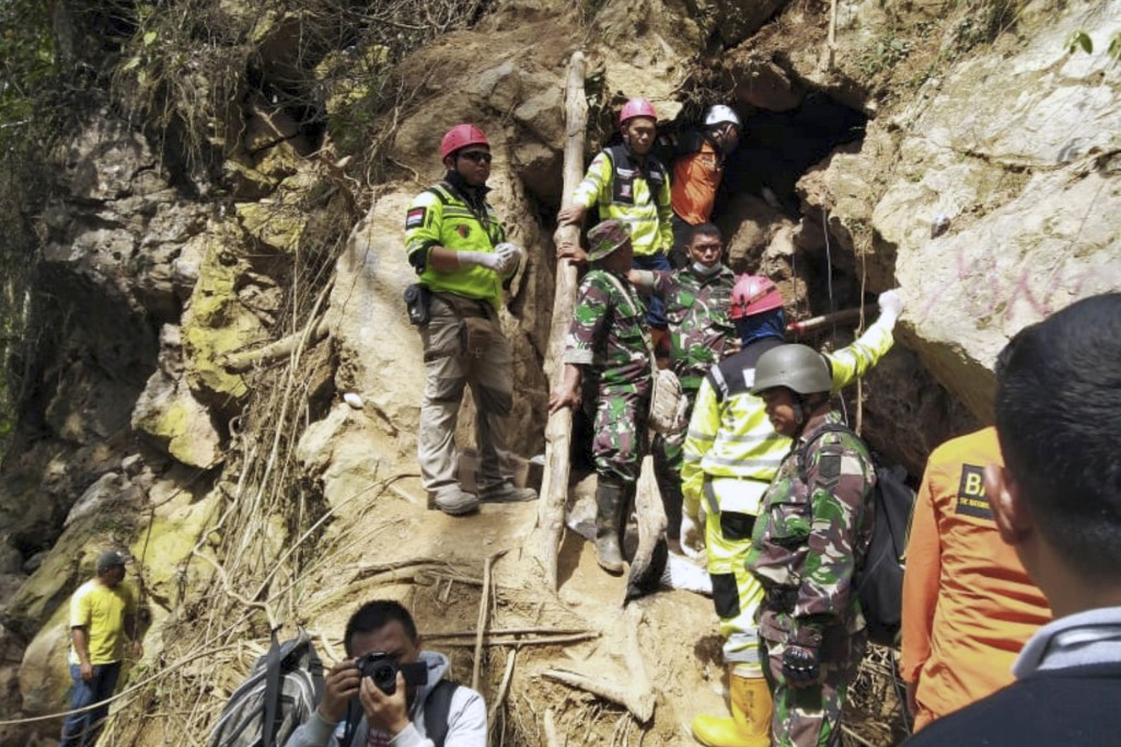 Rescuers stand at the entrance of a collapsed mine in Bolaang Mongondow, North Sulawesi, Indonesia, Thursday, Feb. 28, 2019. Rescue workers used makes