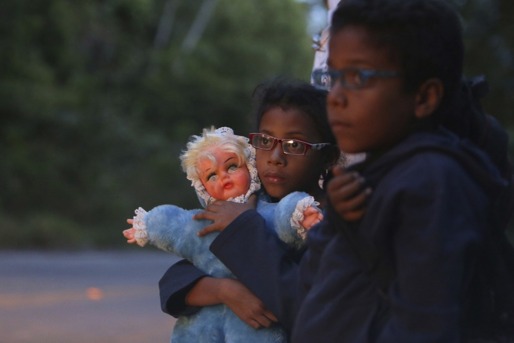 FILE - In this March 9, 2018 file photo, 9-year-old Ashley Angelina holds her doll as she hitch-hikes with her twin brother Angel David and parents af