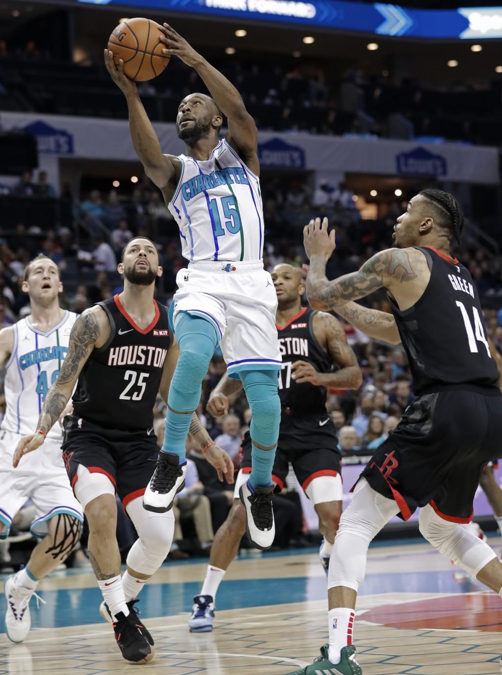 Charlotte Hornets' Kemba Walker (15) shoots between Houston Rockets' Austin Rivers (25) and Gerald Green (14) during the first half of an NBA basketba