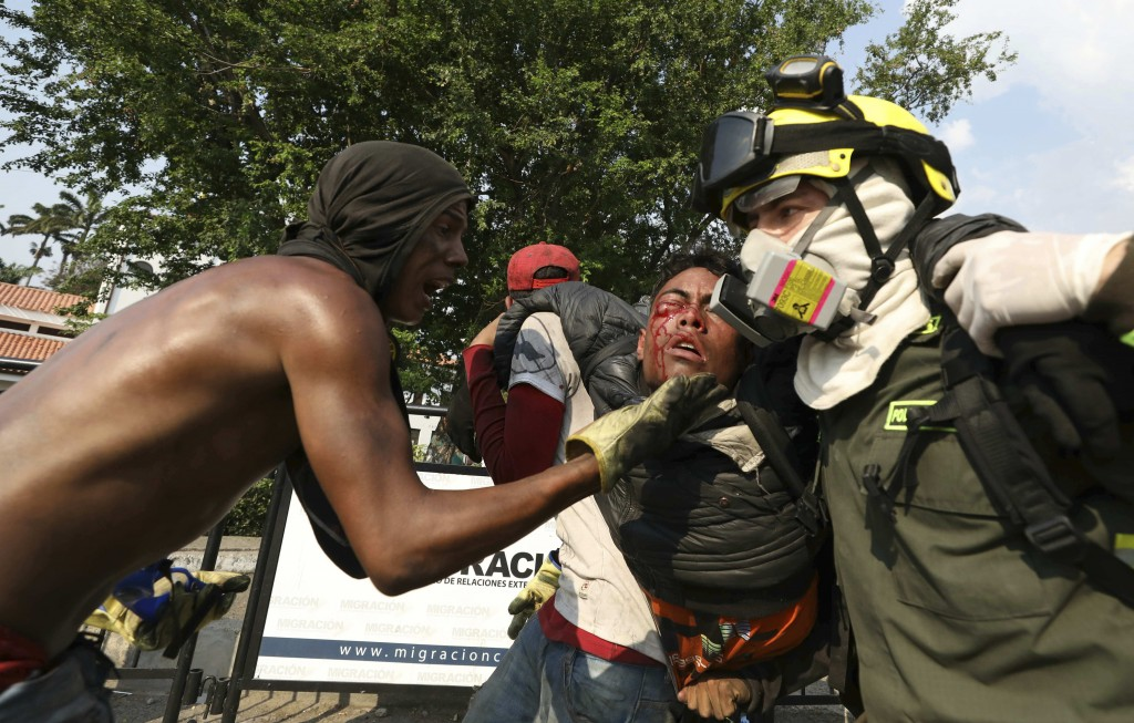 FILE - In this Feb. 25, 2019 file photo, a Venezuelan youth, injured in clashes with Venezuelan National Guardsmen, is carried to a safe zone, at the