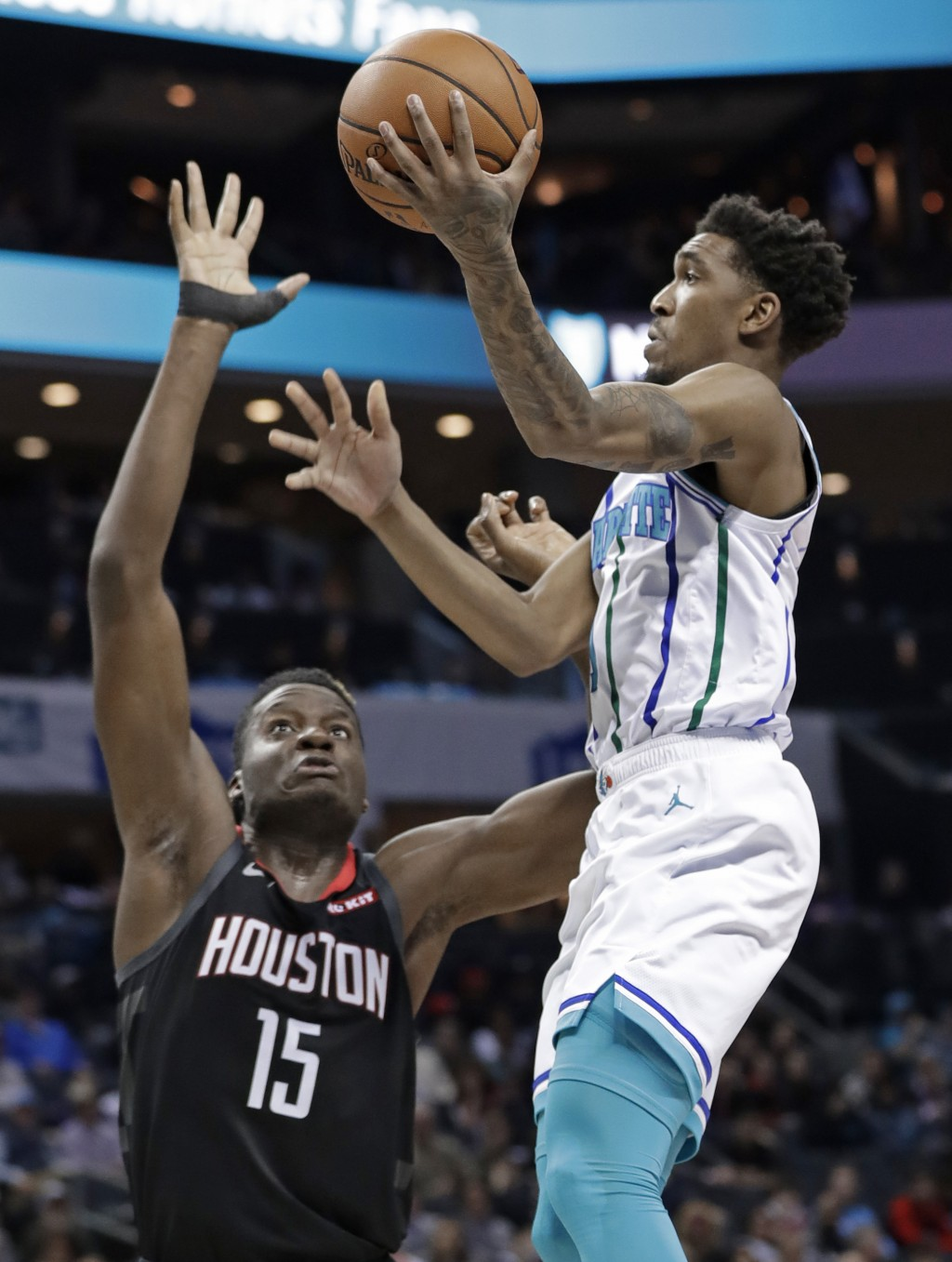 Charlotte Hornets' Malik Monk, right, shoots against Houston Rockets' Clint Capela, left, during the first half of an NBA basketball game in Charlotte