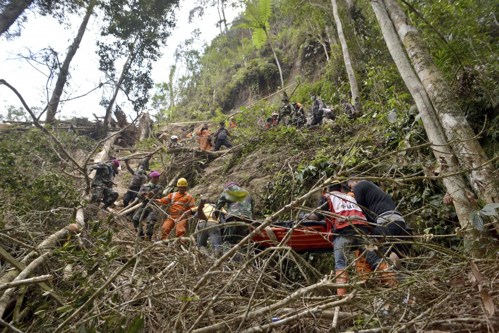 Rescuers carry a survivor of a collapsed mine on a stretcher through a steep terrain in Bolaang Mongondow, North Sulawesi, Indonesia, Thursday, Feb. 2...