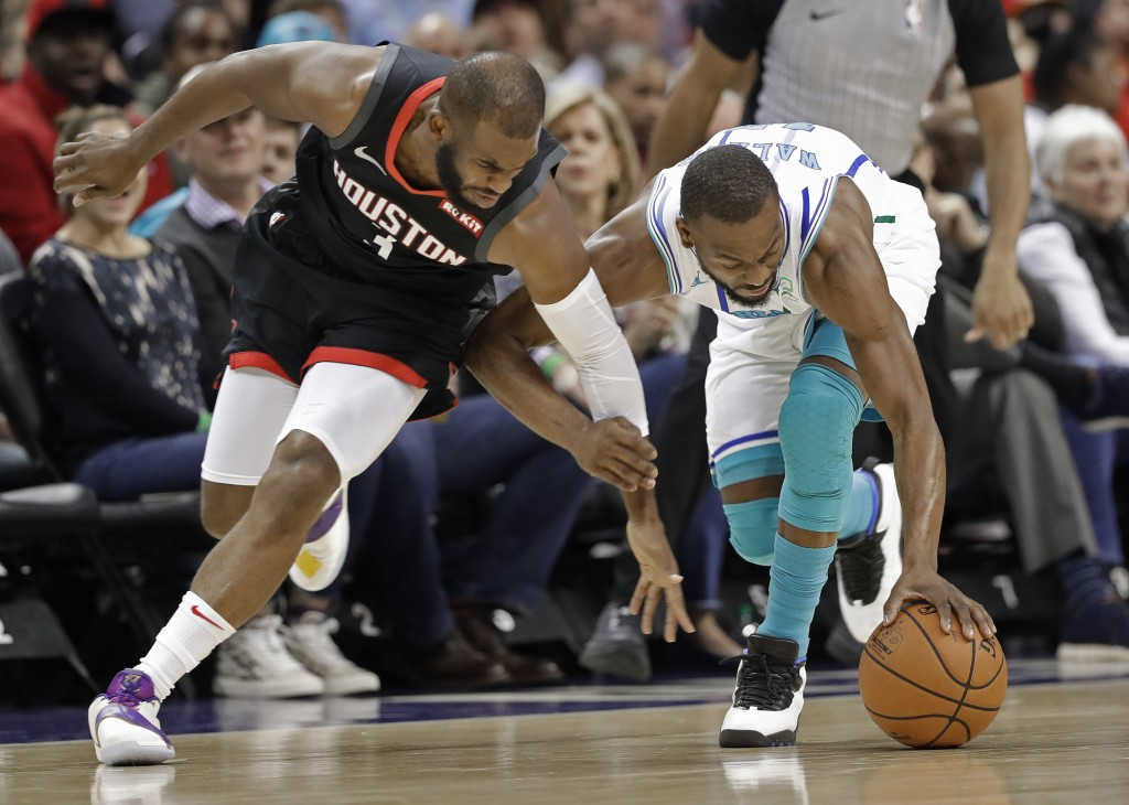 Charlotte Hornets' Kemba Walker, right, and Houston Rockets' Chris Paul, left, chase a loose ball during the first half of an NBA basketball game in C