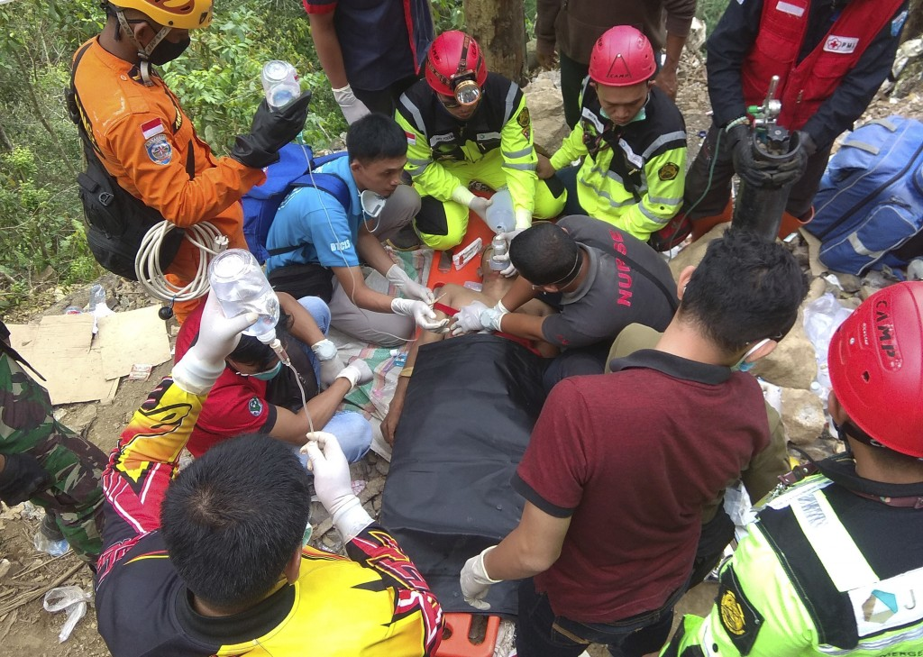Rescuers perform emergency resuscitation on a victim of a collapsed mine on a stretcher in Bolaang Mongondow, North Sulawesi, Indonesia, Thursday, Feb
