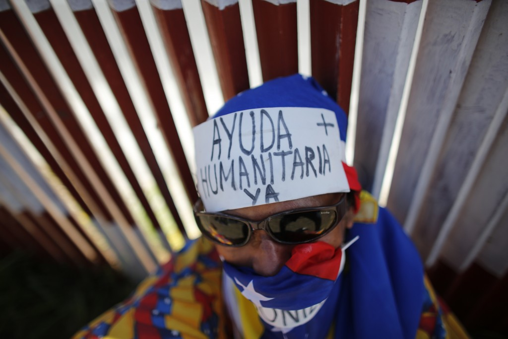 "FILE - In this Feb. 23, 2019 file photo, an opposition supporter wears a message on his forehead that reads in Spanish: ""Humanitarian aid now"" during"