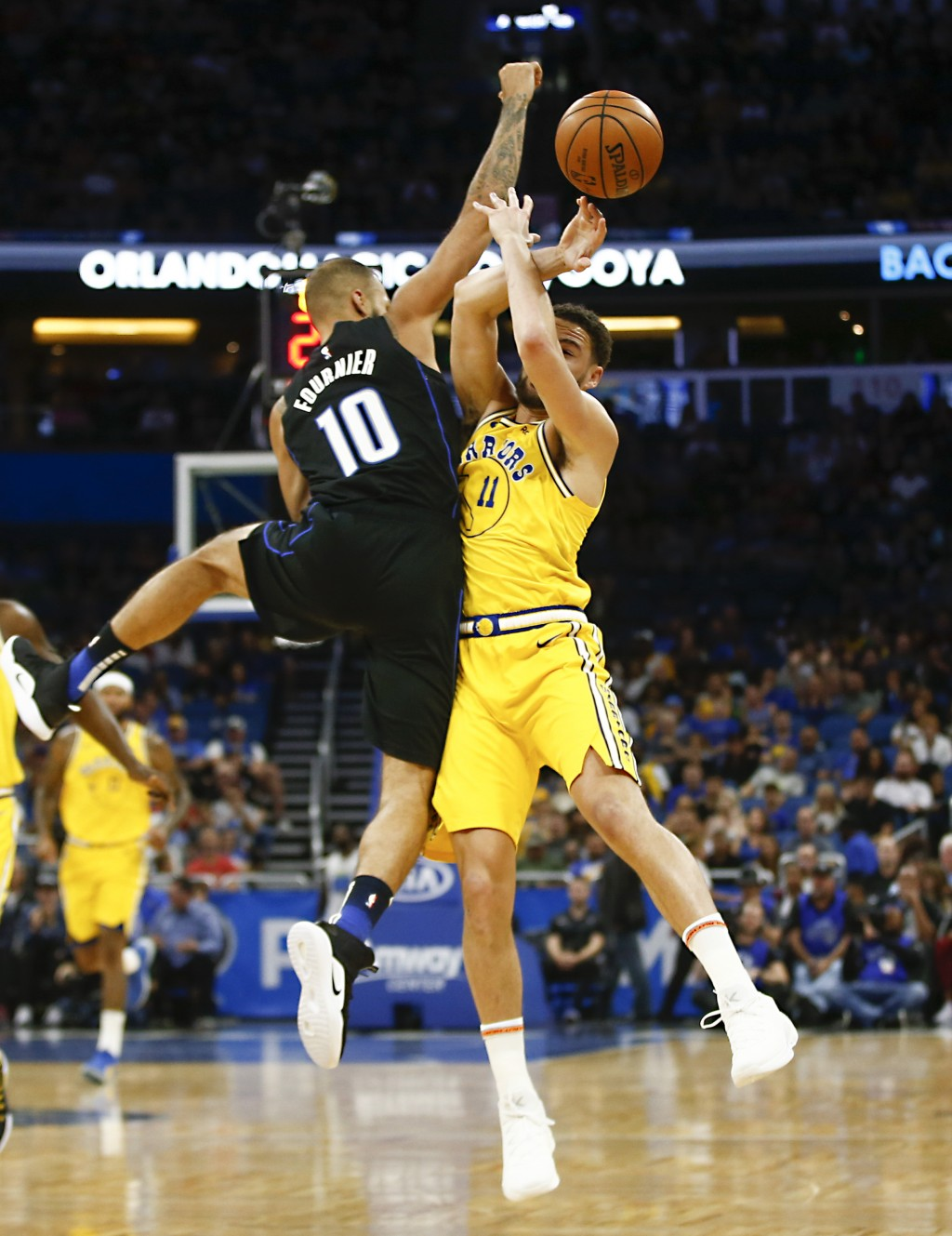 Orlando Magic guard Evan Fournier (10) fouls Golden State Warriors guard Klay Thompson (11) during the first quarter of an NBA basketball game in Orla...