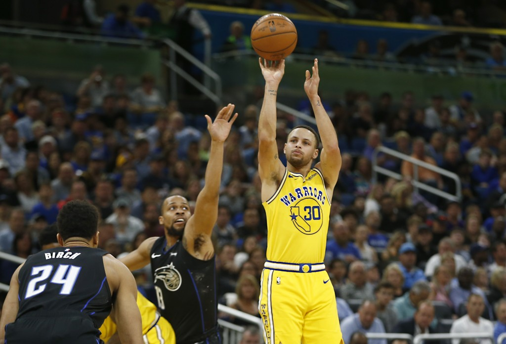 Orlando Magic guard Isaiah Briscoe (13) tries to block the shot from Golden State Warriors guard Stephen Curry (30) as Magic center Khem Birch (24) lo...