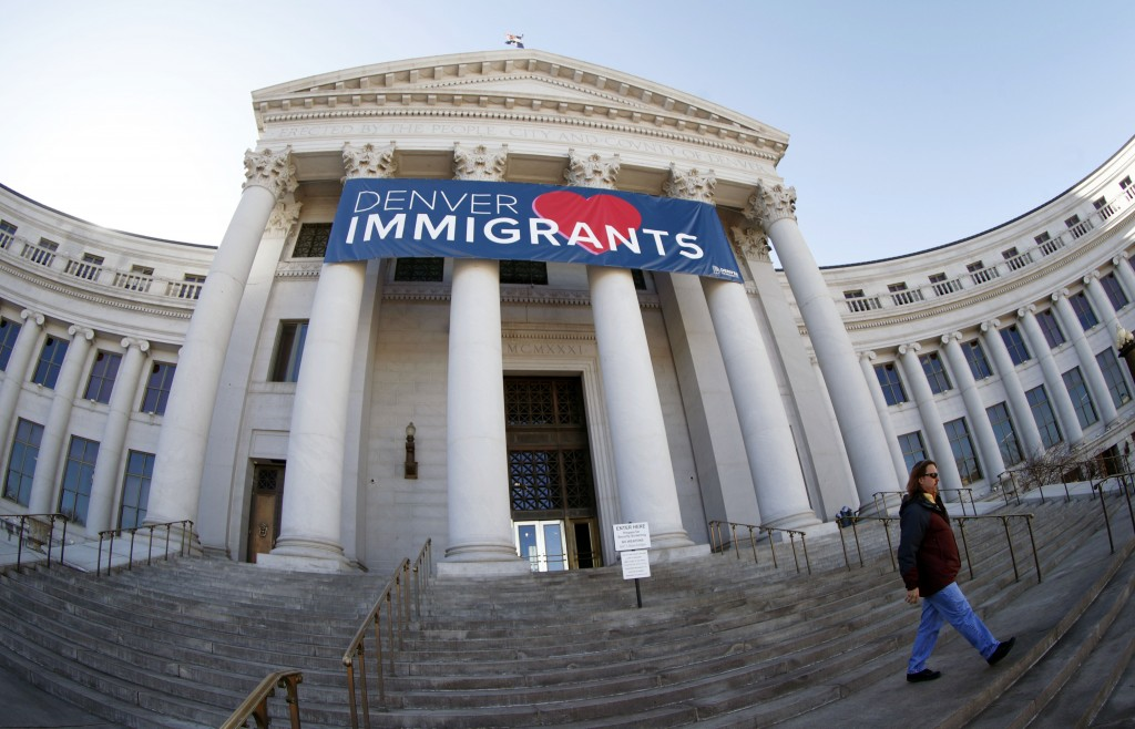 FILE - In this Feb. 26, 2018 file photo, a banner to welcome immigrants is shown through a fisheye lens over the main entrance to the Denver City and ...