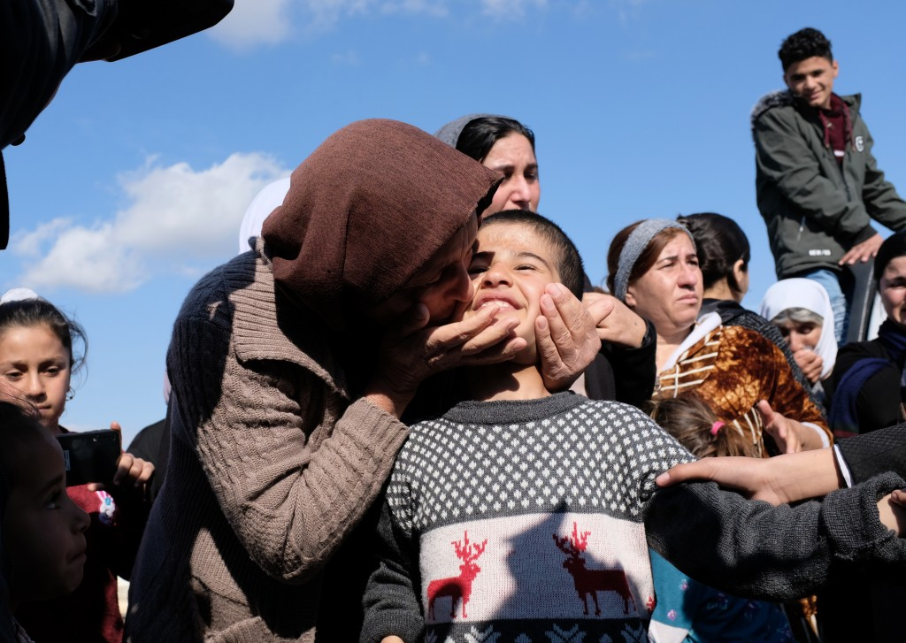 Dilbar Ali Ravu, 10, is kissed by his aunt Dalal Ravu after Yazidi children were reunited with their families in Iraq after five years of captivity wi
