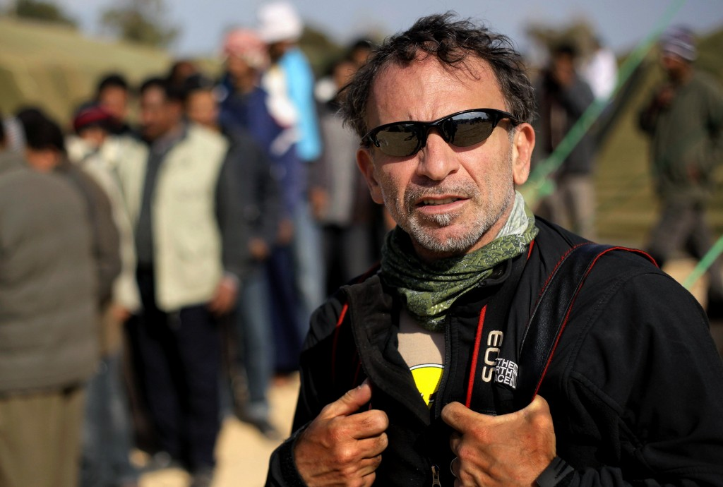 In this photo taken on Friday, Feb. 25, 2011, Greek photojournalist Yannis Behrakis works at a refugee camp set up by the Tunisian army, at the Tunisi