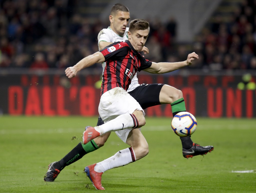 FILE - In this Saturday, March 2, 2019 file photo, AC Milan's Krzysztof Piatek, foreground, and Sassuolo's Merih Demiral vie for the ball during their