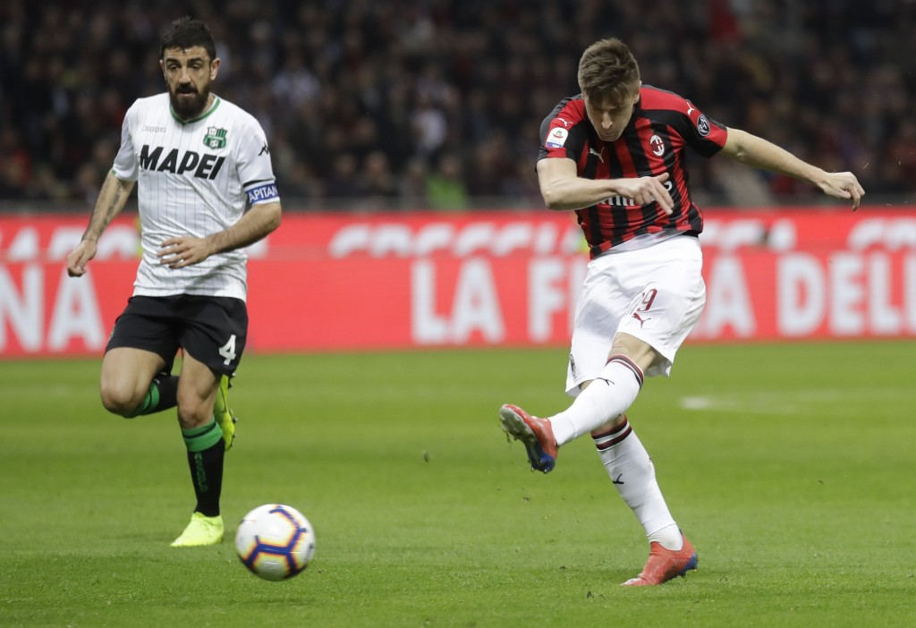 FILE - In this Saturday, March 2, 2019 file photo, AC Milan's Krzysztof Piatek fires a shot past Sassuolo's Francesco Magnanelli during the Serie A so