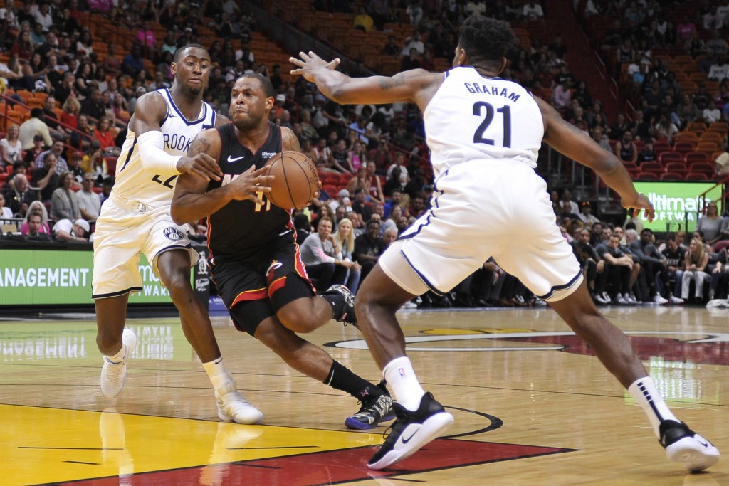 Miami Heat guard Dion Waiters drives past Brooklyn Nets guards Caris LeVert and Treveon Graham during the first half of an NBA basketball game at the
