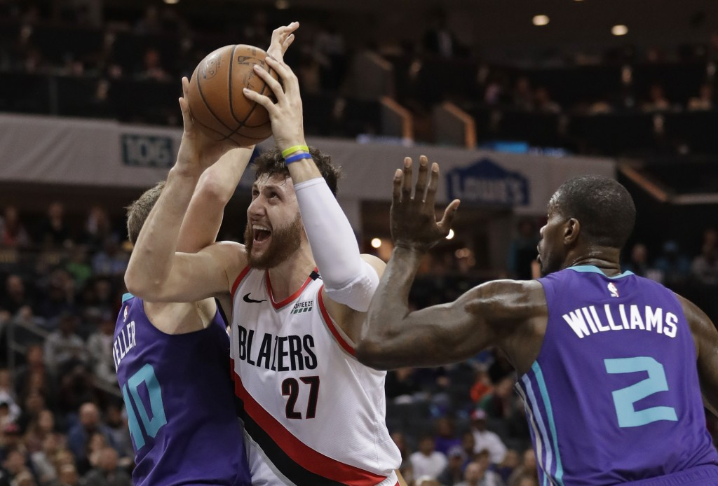 Portland Trail Blazers' Jusuf Nurkic (27) drives between Charlotte Hornets' Marvin Williams (2) and Cody Zeller (40) during the first half of an NBA b