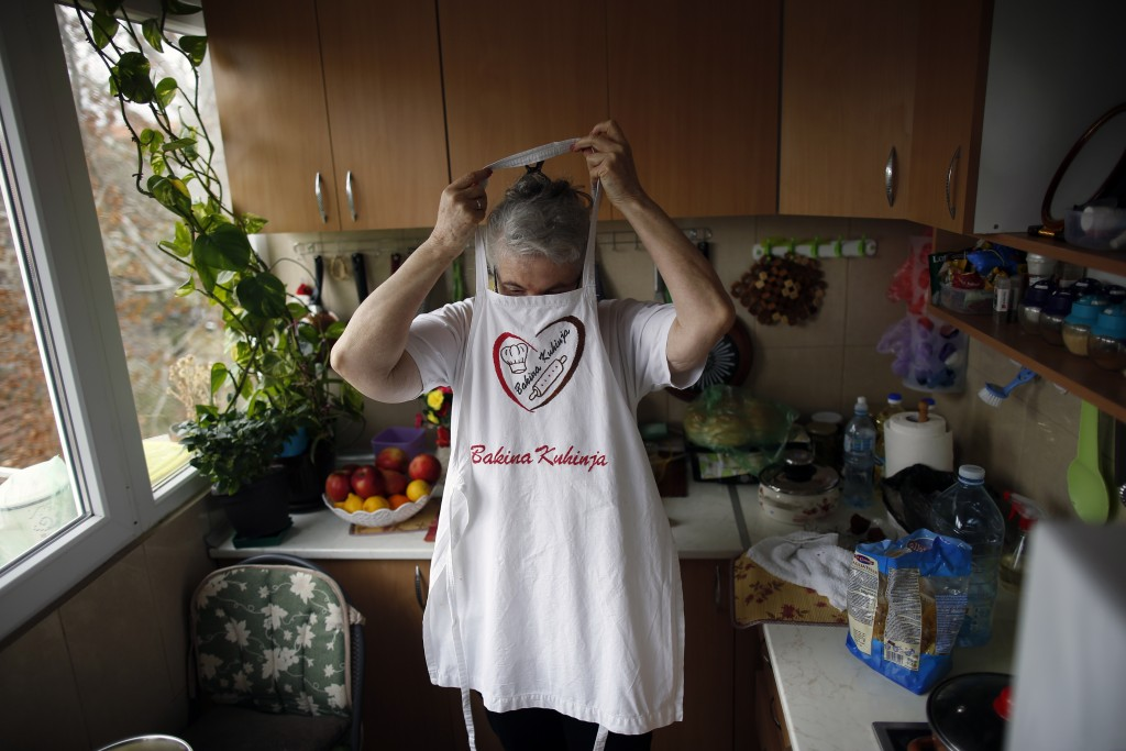 Jelena Petrovic puts on an apron with a print reading ''Granny's kitchen'' in her home in Jagodina, Serbia, Tuesday, Feb. 12, 2019. Serbs looking for