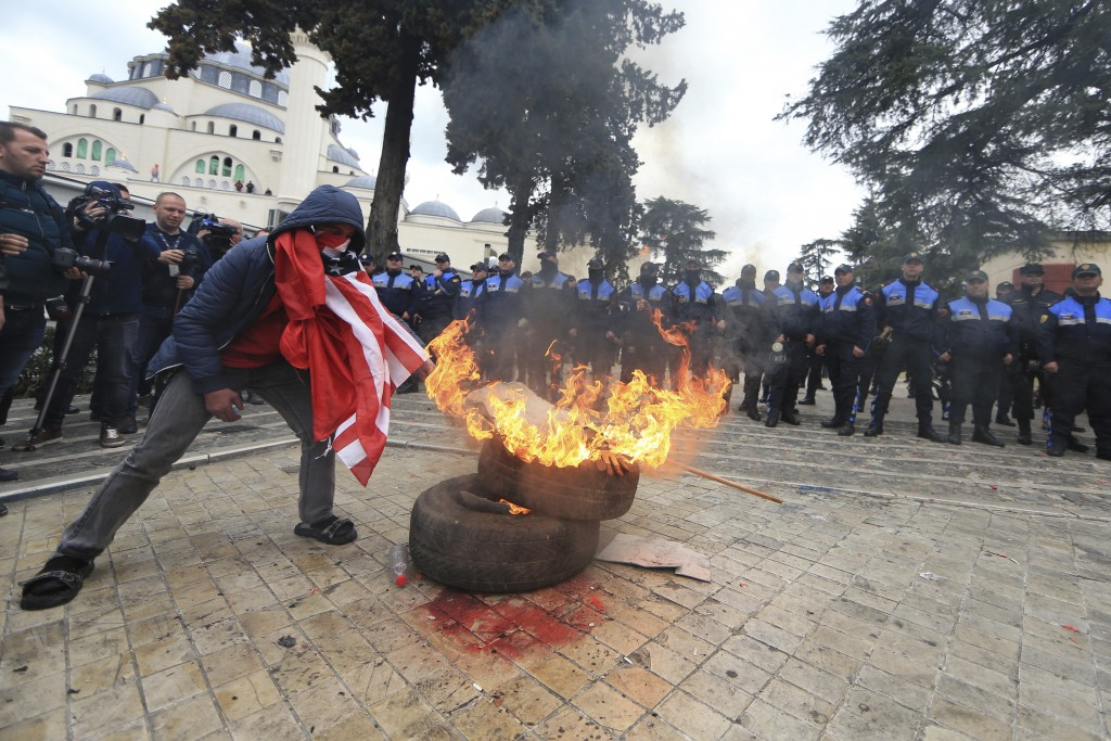 Protesters burn tyres outside the parliament building during an anti-government rally , in Tirana , Albania, Tuesday, March 5, 2019. Albania's opposit...