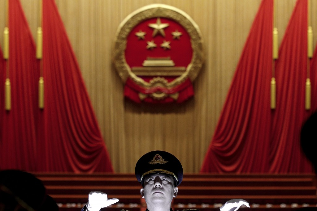 A Chinese military conductor instructs his music band members during a rehearsal for the opening session of the China's National People's Congress at ...
