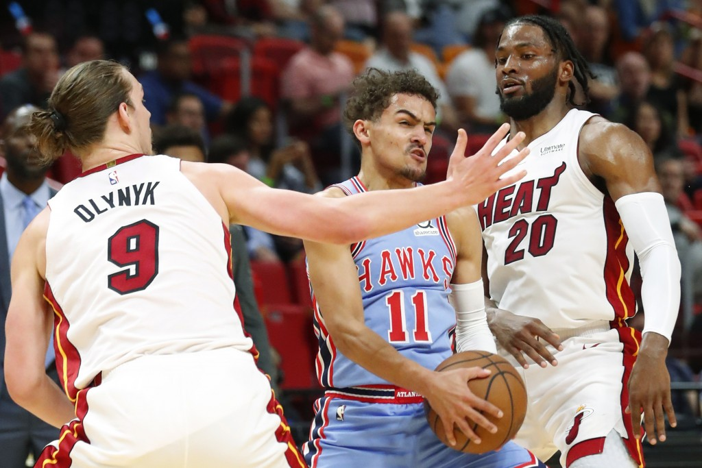 Atlanta Hawks guard Trae Young (11) looks for an opening past Miami Heat forwards Kelly Olynyk (9) and Justise Winslow (20) during the first half of a