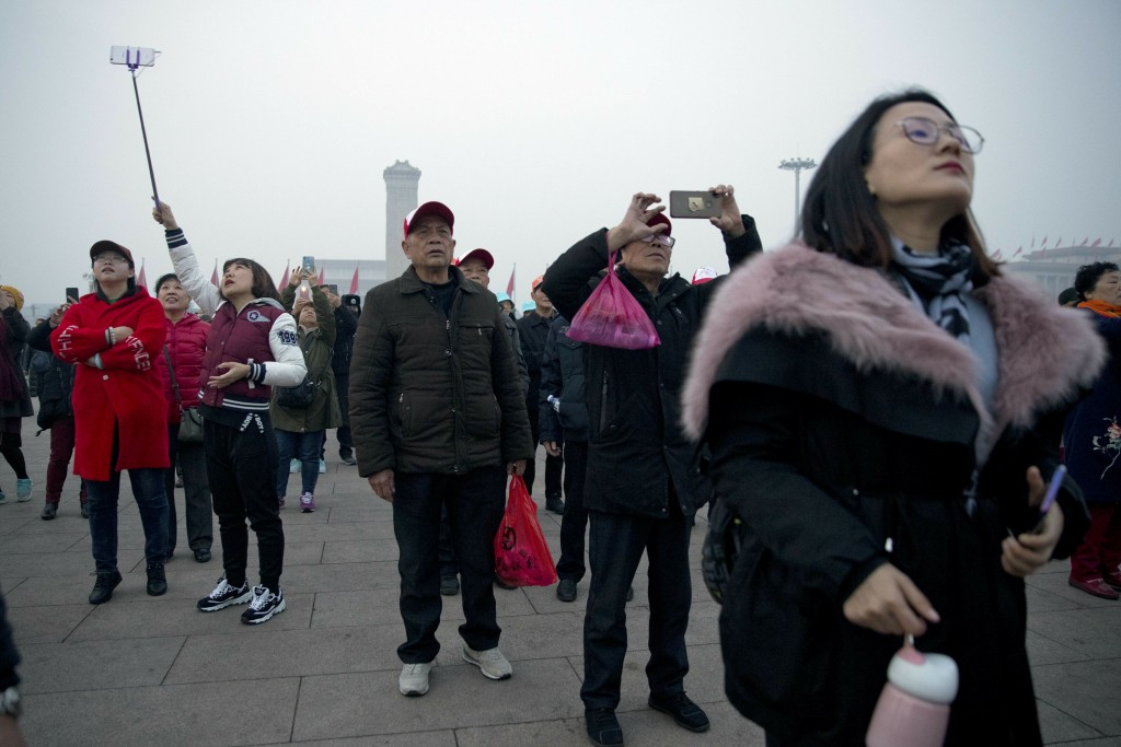 Tourists take photos of the daily flag raising ceremony at Tiananmen Square on the eve of the opening session of China's National People's Congress (N...